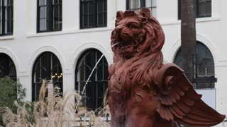 A daytime establishing shot of a lion water fountain in a southern American city.