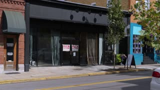 A daytime establishing shot of an empty storefront for rent in the business district in a small town in America.