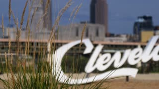 A daytime establishing shot of the iconic Cleveland script sign as seen through tall grass on a summer day. Shallow DOF.