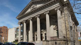 A daytime exterior (DX) establishing shot of a grand church building with large Roman pillars at the entrance.