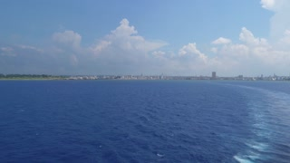 A daytime extreme wide establishing shot of the shoreline of Havana, Cuba as seen from a departing cruise liner.