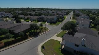 A daytime rising aerial establishing shot of a typical San Antonio, Texas residential neighborhood.