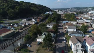 A daytime slowly moving forward aerial establishing shot of a typical Pennsylvania small town neighborhood district.