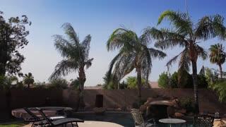 A daytime summer establishing shot of a typical Arizona residential backyard on a windy day. Phoenix suburbs.