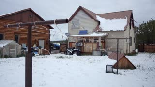 A daytime wintry establishing shot of a Colorado suburban home and backyard.