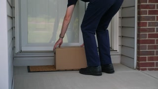 A delivery man places a cardboard box on a home's front porch then rings the doorbell before leaving.