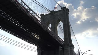 A dramatic backlit low angle view from under the Brooklyn Bridge on a summer day.	Shot at 48fps.