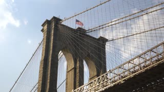 A dramatic low angle view from under the Brooklyn Bridge on a summer day.