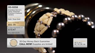 A fictional, QVC-like home shopping television content screen. Slowly rotating golden jewelry items with hypothetical graphics along the sides.