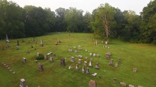 A forward high angle aerial above a historic cemetery in the woods.