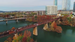 A high angle daytime exterior establishing shot of the skyline of Austin, Texas with a railroad bridge over the Colorado River in the foreground.