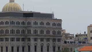A high angle dolly establishing shot of the capitol dome in the old town section of Havana, Cuba.