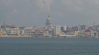 A high angle dolly establishing shot of the Havana, Cuba skyline with the capitol dome in the old town section in the distance.