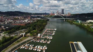 A high angle right moving aerial establishing shot of a marina on the Monongahela River with the Pittsburgh skyline in the distance.