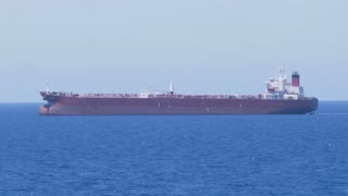 A large cargo freighter ship on the horizon at sea.