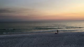 A lone woman packs up her gear after a day at the beach in Destin, Florida.