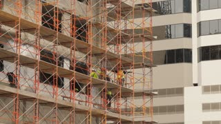 A long shot of construction workers on scaffolding on the side of a building in a large city.