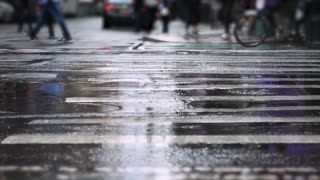 A low angle slow motion view of traffic on a rainy Manhattan street.