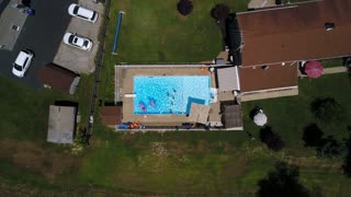 A lowering bird's eye aerial view of a typical backyard household pool on a sunny summer day. Pittsburgh suburbs.