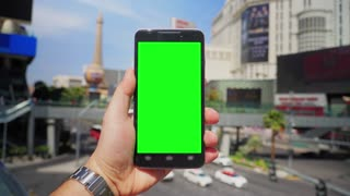 A man holds a smartphone outside above Las Vegas Boulevard as traffic and taxis pass by in the background. Green screen with optional corner pin markers for advanced screen replacement. Shot at 60fps.