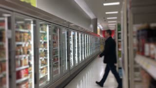A man in a grocery store shops in the frozen foods section.