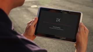 A man slowly downloads a file over 1X cellular data on his handheld tablet.