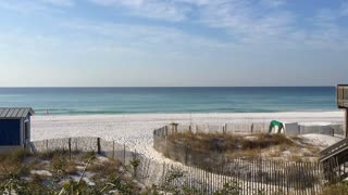 A man walks at the shoreline at a Destin, Florida beach.