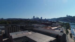A morning aerial establishing shot of the Pittsburgh skyline with the warehouse business industrial park in the foreground.
