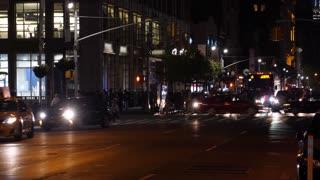 A night time view of pedestrians in a Manhattan 6th Avenue crosswalk.