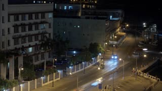 A night timelapse view of traffic in the city of Havana, Cuba and the shoreline of Havana Port Bay.