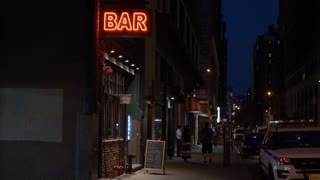 A nighttime exterior establishing shot of a bar and restaurant in downtown Manhattan, New York City.