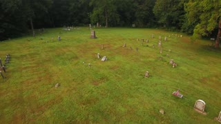 A reverse low angle aerial above a historic cemetery in the woods.