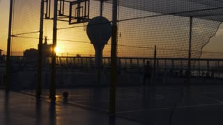 A silhouetted man plays basketball on the deck of a large cruise ship at sunset. Shot at 48fps.
