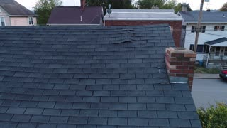 A simulated video feed of a roof inspector's unmanned drone examining a home's damaged shingled roof after a storm.