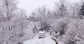 A slow aerial dolly shot of a backyard's snowy winter wonderland.