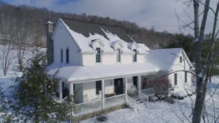 A slow aerial reverse establishing shot of a typical snow-covered Pennsylvania rural farmhouse in Winter.