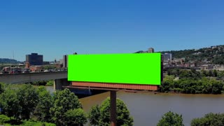 A slow push forward aerial view of a city's billboard. Green screen with optional tracking points for advanced screen replacement. Veterans Bridge over the Allegheny River in the background. Billboard is 4000x1080.