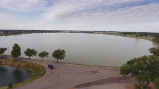 A slow rising aerial establishing shot of the Altus City Reservoir. The town of Altus, Oklahoma is in the distance.