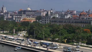 A slowly moving aerial dolly establishing shot of traffic and buildings on the El Malecón in downtown Havana, Cuba.