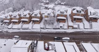 A slowly moving backwards aerial winter view of a typical Western Pennsylvania residential neighborhood during a snowstorm.