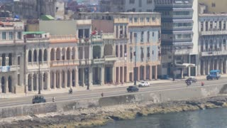 A slowly moving dolly establishing shot of traffic and buildings on the El Malecón in downtown Havana, Cuba.