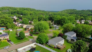 A slowly rising aerial establishing shot of a typical Pennsylvania residential neighborhood on a sunny summer day. Pittsburgh suburbs.
