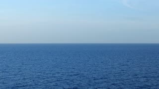 A slowly zooming out view of a cruise ship's porthole overlooking the open ocean and horizon.
