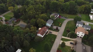 A summer overcast daytime aerial establishing shot of a typical Western Pennsylvania residential neighborhood.