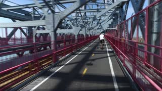 A unique fast forward perspective of a pedestrian or bicyclist traveling on the Williamsburg Bridge.