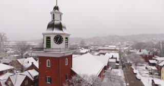AMBRIDGE, PA - Circa March, 2017 - A slowly moving ahead snowy establishing shot of St. John's Lutheran Church in Old Economy Village.