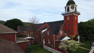 AMBRIDGE, PA - Circa March, 2017 - A slowly rising summer evening establishing shot of St. John's Lutheran Church in Old Economy Village.