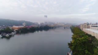 An early morning foggy aerial establishing shot of the Pittsburgh skyline with the Steel Building poking up above the fog. The Allegheny River is in the foreground.