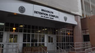 An evening establishing shot of the front entrance to the Brooklyn Detention Center and police station.