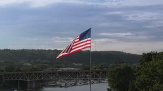 An evening slow motion aerial view of a large American Flag blowing in the wind with the small town of Beaver, Pennsylvania in the distance. Pittsburgh suburbs.